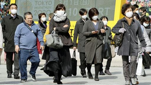 In Tokios Einkaufsviertel Ginza tragen Passanten einen Mundschutz.