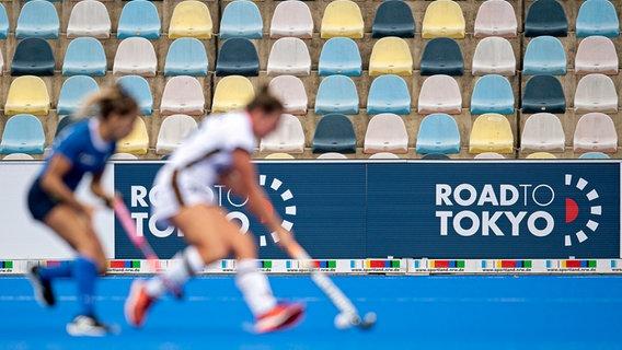 """Hockey-Spielerinnen vor leeren Rängen und einer Bande mit der Aufschrift """"Road to Tokyo"""". Viele Sportler wissen derzeit nicht, wohin sie der Weg zu Olympia tatsächlich führen wird (Symbolbild). © imago images / Sven Simon"""