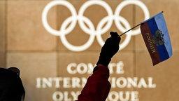 Eine Frau schwenkt eine russische Fahne vor den olympischen Ringen am Hauptquartier des Internationalen Olympischen Komitees (IOC) in Lausanne (Symbolbild).