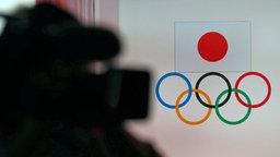 Ein Kameramann filmt die Olympischen Ringe und die japanische Flagge.