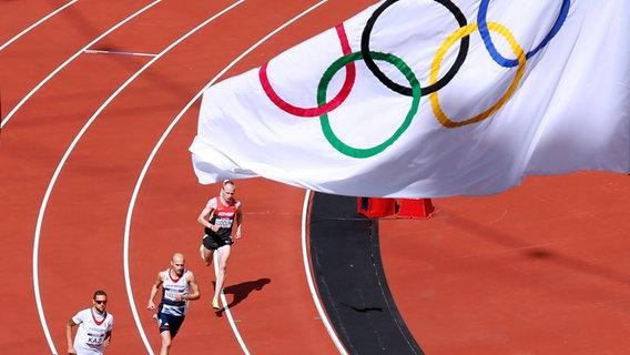 Im Olympiastadion von London 2012 messen sich Läufer unter einer Fahne mit den Olympischen Ringen. © imago images / Laci Perenyi