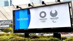 Eine Hinweistafel auf die Olympischen Spiele steht in Tokio.