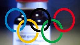 Symbolbild Doping: Olympische Ringe vor einer Flasche Test Prop 100 Steroid
