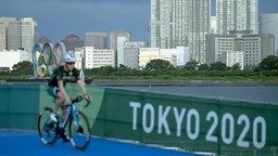 """Ein Triathlet fährt vor dem Start auf dem Fahrrad an einem Banner mit der Aufschrift """"Tokyo 2020"""" vorbei."""