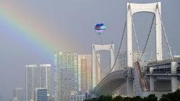 Impressionen aus der Olympiastadt Tokio mit einem Heißluftballon und einem Regenbogen über der Rainbow Bridge.