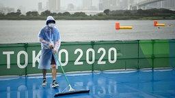 Helfer schieben bei Regen Wasser von der olympischen Triathlon-Strecke in Tokio.