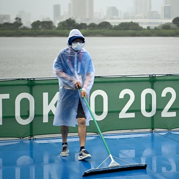 Helfer schieben bei Regen Wasser von der olympischen Triathlon-Strecke in Tokio. | dpa-Bildfunk