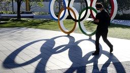 Die Olympischen Ringe vor dem Nationalstadion in Japan werfen Schatten.