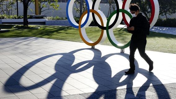 Die Olympischen Ringe vor dem Nationalstadion in Japan werfen Schatten. © picture alliance / kyodo / dpa
