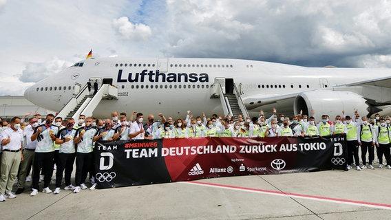 Das deutsche Team steht nach seiner Ankunft von den Olympischen Spielen in Tokio auf dem Flughafen vor einer Maschine der Lufthansa. © dpa-Bildfunk