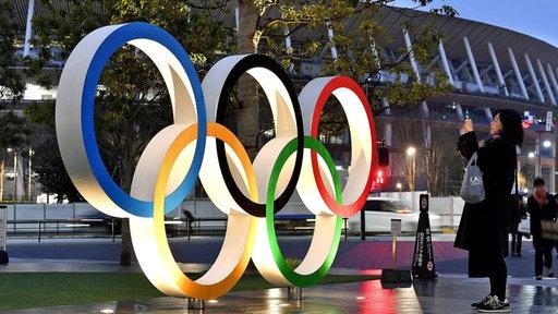 Eine Frau fotografiert die beleuchteten Olympischen Ringe vor dem Nationalstadion in Tokio.