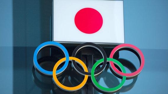 Symbolbild mit den Olympischen Ringen und der japanischen Flagge. © picture alliance/Morio Taga/Jiji Press Photo/dpa Foto: Morio Taga