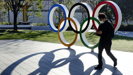 Eine Mann mit Mundschutz läuft an einem Aufsteller mit den Olympischen Ringen vorbei. © picture alliance / dpa