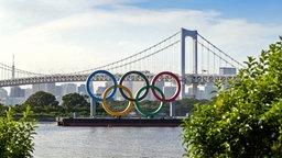 Die Olympischen Ringe vor der Rainbow Bridge am Odaiba Marine Park