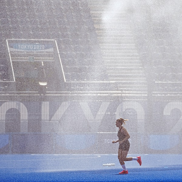 Eine deutsche Spielerin läuft vor Spielbeginn in Tokio durch den Sprühregen der Platzbewässerung. | dpa picture alliance