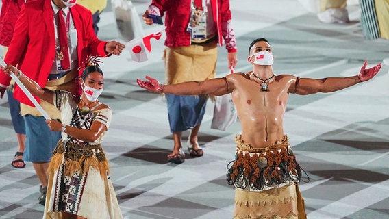 Die Fahnenträger von Tonga, Malia Paseka und Taekwondokämpfer Pita Taufatofua, führen das Team bei der Eröffnungsfeier der Olympischen Spiele 2020 in das Olympiastadion. © picture alliance/dpa Foto:  Michael Kappeler
