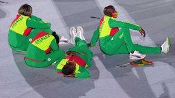 Bei der Eröffnungsfeier im Olympiastadion von Tokio sitzen vier Athleten aus Grenada auf dem Boden.