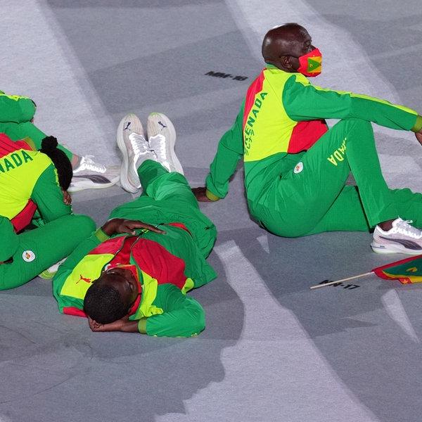 Bei der Eröffnungsfeier im Olympiastadion von Tokio sitzen vier Athleten aus Grenada auf dem Boden. | picture alliance