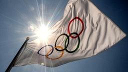 Eine Fahne mit den Olympischen Ringen, dahinter die hoch stehende Sonne