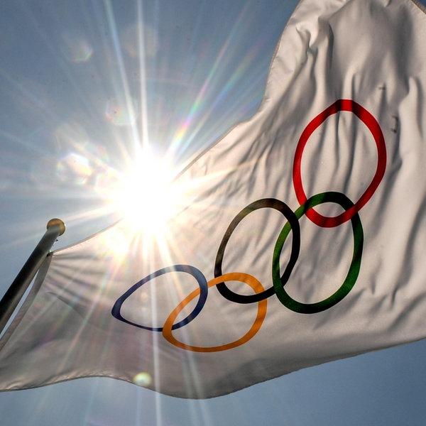 Eine Fahne mit den Olympischen Ringen, dahinter die hoch stehende Sonne   picture alliance