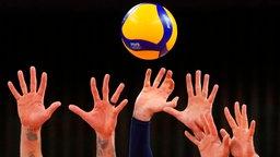 US-amerikanische Volleyball-Spieler versuchen einen Ball zu blocken.