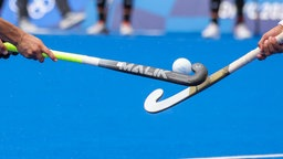 Zwei Hockeyschläger treffen bei dem Kampf um den Ball aufeinander.