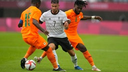 Marco Richter (M) aus Deutschland kämpft mit Ismael Diallo (r) und Max Gradel (l) um den Ball.