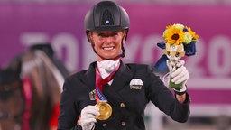 Die deutsche Dressurreiterin Jessica von Bredow-Werndl präsentiert ihre Goldmedaille.
