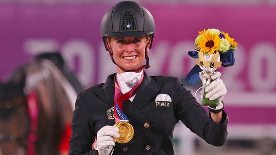 Die deutsche Dressurreiterin Jessica von Bredow-Werndl präsentiert ihre Goldmedaille. © dpa-Bildfunk Foto: Friso Gentsch/dpa