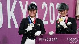 Die deutschen Dressurreiterinnen Isabell Werth (l.) mit ihrer Silbermedaille und Jessica von Bredow-Werndl mit ihrer Goldmedaille.