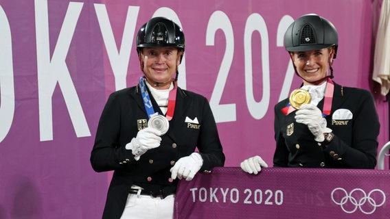 Die deutschen Dressurreiterinnen Isabell Werth (l.) mit ihrer Silbermedaille und Jessica von Bredow-Werndl mit ihrer Goldmedaille. © picture alliance/dpa Foto: Friso Gentsch