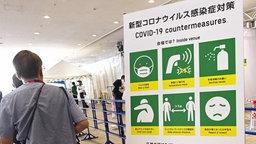 Ein Hinweisschild in Tokio zu Covid-19 Maßnahmen.