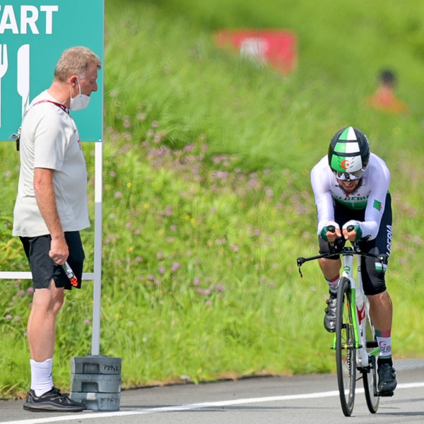 Patrick Moster, Sportdirektor vom Bund Deutscher Radfahrer, steht am Streckenrand neben dem algerischen Radsportler Azzedine Lagab.   picture alliance