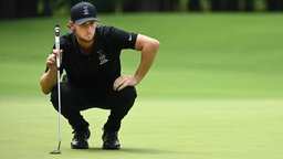 Der belgische Golfer Thomas Pieters  in der Hocke