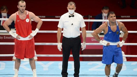 Der deutsche Boxer Ammar Riad Abduljabbar (r.) bei der Urteilsverkündung nach dem Kampf gegen den Russen Muslim Gamsatowitsch. © dpa-bildfunk