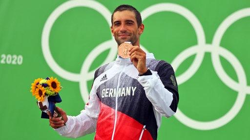 Der deutsche Kanute Hannes Aigner präsentiert seine Bronzemedaille.