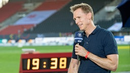 ARD-Leichtathletik-Experte Frank Busemann steht mit einem Mikrofon in der Hand in einem Stadion.