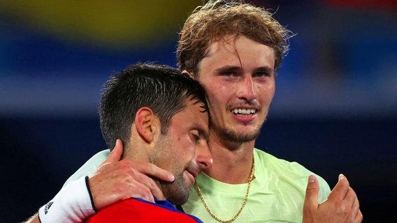 Der deutsche Tennis-Spieler Alexander Zverev (r.) jubelt üben den Einzug ins Finale, während der Serbe Novak Djokovic ihm im Arm liegend gratuliert. © dpa-Bildfunk Foto: Jan Woitas/dpa-Zentralbild/dpa