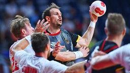 Der deutsche Handballer Kai Häfner führt den Ball und sucht einen Mitspieler.