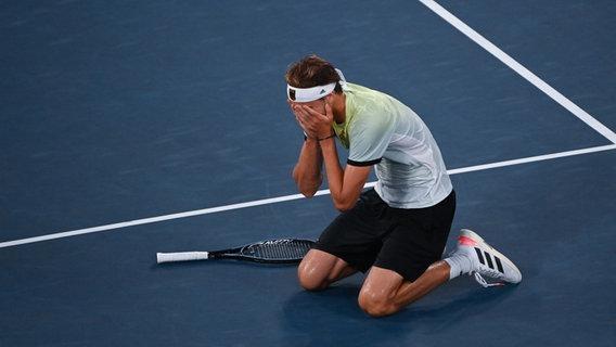 Der deutsche Tennispieler Alexander Zverev kniet sich hin und hält die Hände vor Freude ans Gesicht. © dpd-bildfunk
