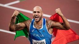 Der 100m Läufer Lamont Marcell Jacobs aus Italien jubelt mit der Nationalflagge.