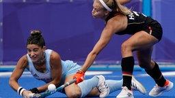Die argentinische Spielerin Maria Victoria Granatto fällt beim Kampf um den Ball gegen die deutsche Spielerin Kira Horn (r).