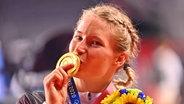 Die deutsche Ringerin Aline Rotter-Focken präsentiert ihre Goldmedaille. © IMAGO / Sven Simon