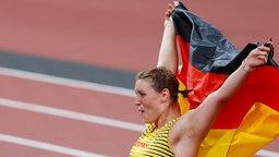 Die deutsche Diskuswerferin Kristin Pudenz jubelt über Silber mit der Nationalflagge.