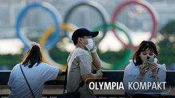 Besucher stehen in der Nähe der im Wasser schwimmenden olympischen Ringe im Odaiba Marine Park in Tokio.