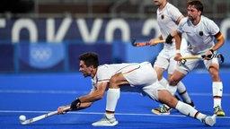 Der deutsche Hockeyspieler Lukas Windfeder schlägt den Ball in einer vorgebeugten Position.