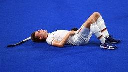 Der deutsche Hockeyspieler Niklas Bosserhoff liegt enttäuscht und erschöpft auf dem Boden