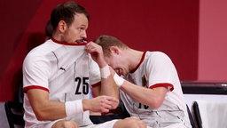 Die deutschen Handballer Kai Häfner (l.) und Timo Kastening reagieren auf die Niederlage.