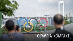 Zwei Männer fotografieren die Olympischen Ringe vor der Regenbogenbrücke in Tokio.
