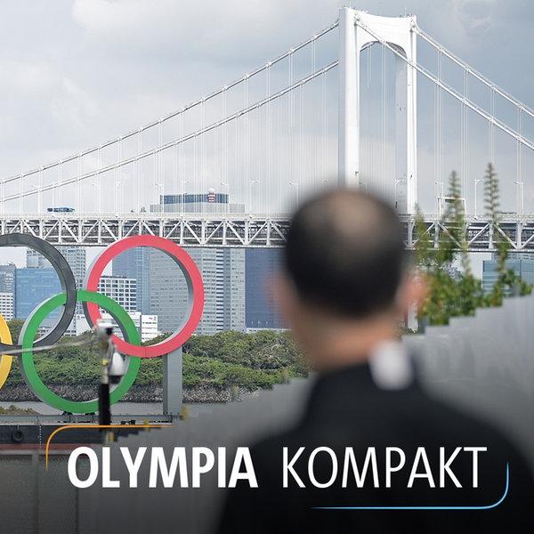 Zwei Männer fotografieren die Olympischen Ringe vor der Regenbogenbrücke in Tokio. | dpa picture alliance